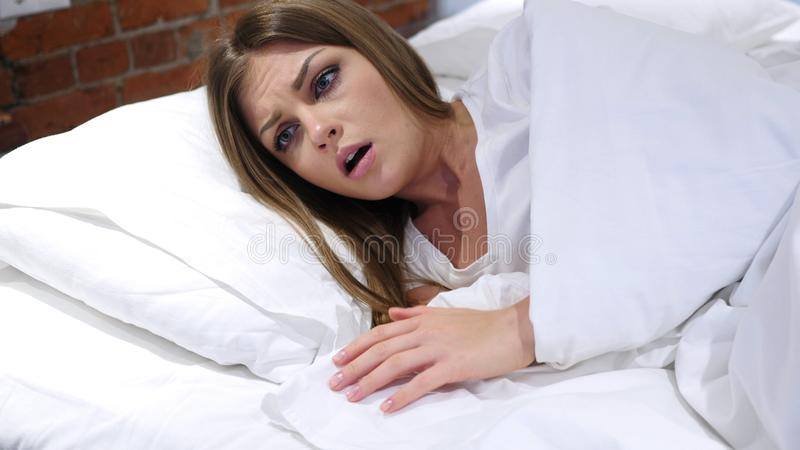 Albtraum, schlafende Frau wacht durch furchtsamen Traum auf lizenzfreies stockfoto