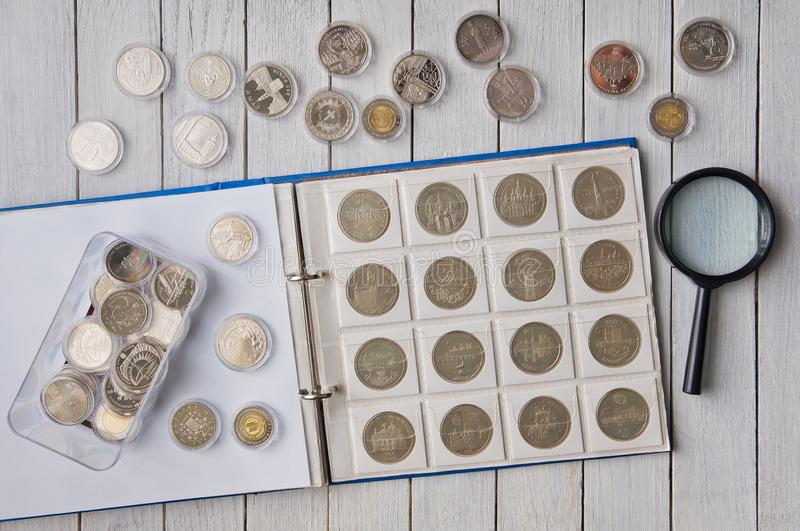 AlbumÂ-with coins and coins in capsules on the Tabelle lizenzfreie stockfotos