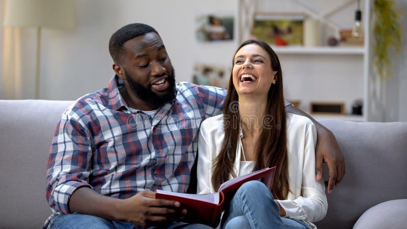 Album photos de visionnement riant de famille de couples sur le sofa, ayant l'amusement, bons souvenirs image libre de droits