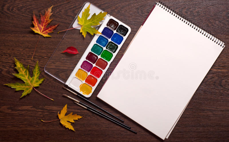 Album, waterverf, borstels en de herfstbladeren stock afbeelding
