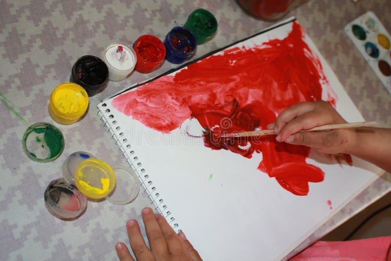 Albumark målarfärger vattenfärg Händer av barnet, 4 yearsold, foto Röd färg på papper Röd målarfärg på albumet Öppna färger C arkivfoto