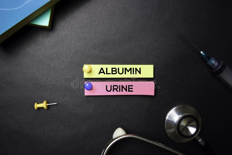 Albumin Urine text on Sticky Notes. Top view isolated on black background. Healthcare/Medical concept stock photos