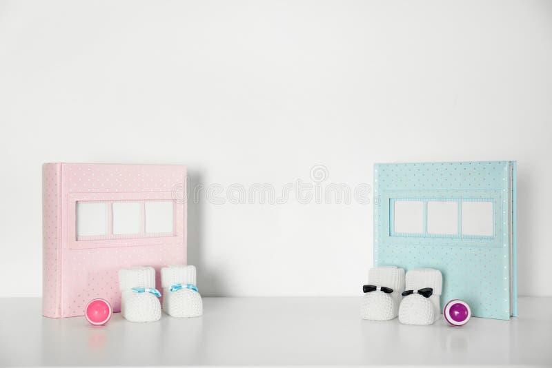 Albums photos avec des petits chaussons et des hochets pour la pièce de bébé intérieure sur la table photos stock