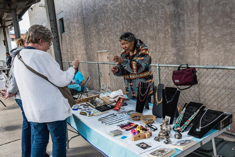 Navajo Jewelry Stand In Albuquerque. Albuquerque, New Mexico / USA / April 1, 2016: Native American woman selling hand crafted jewelry at the train station stock photos