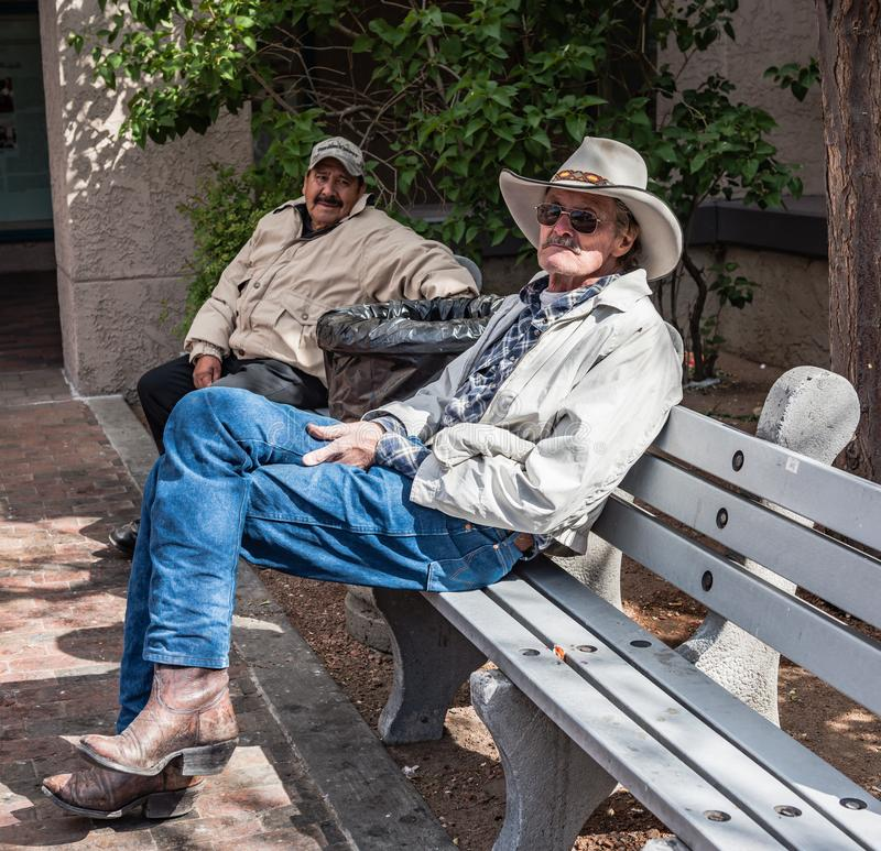 Senior Cowboy of Albuquerque. Albuquerque, New Mexico / USA / April 1, 2016: Rugged older cowboy shares a city bench with a mustached Latino man royalty free stock image