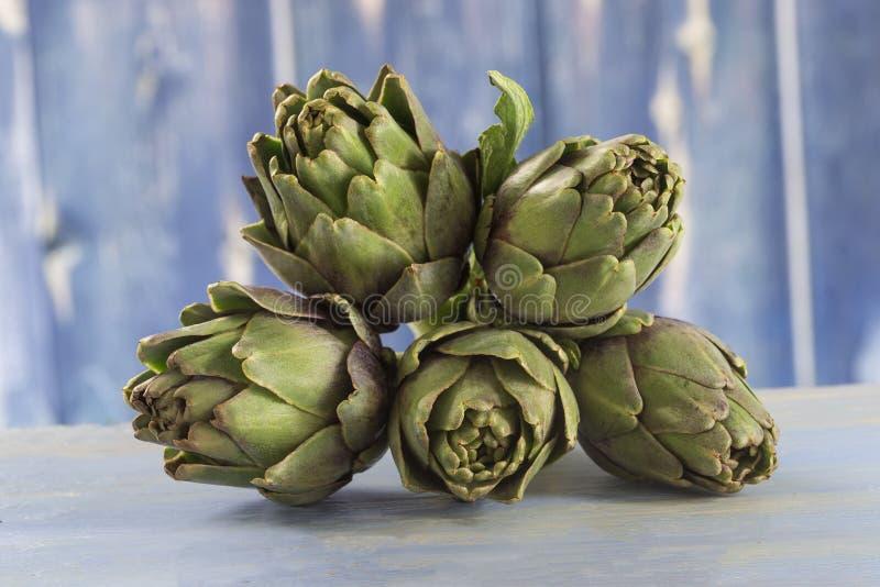 Alcachofas frescas con el tronco y la hoja imagen de archivo