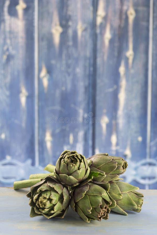 Alcachofas frescas con el tronco y la hoja foto de archivo