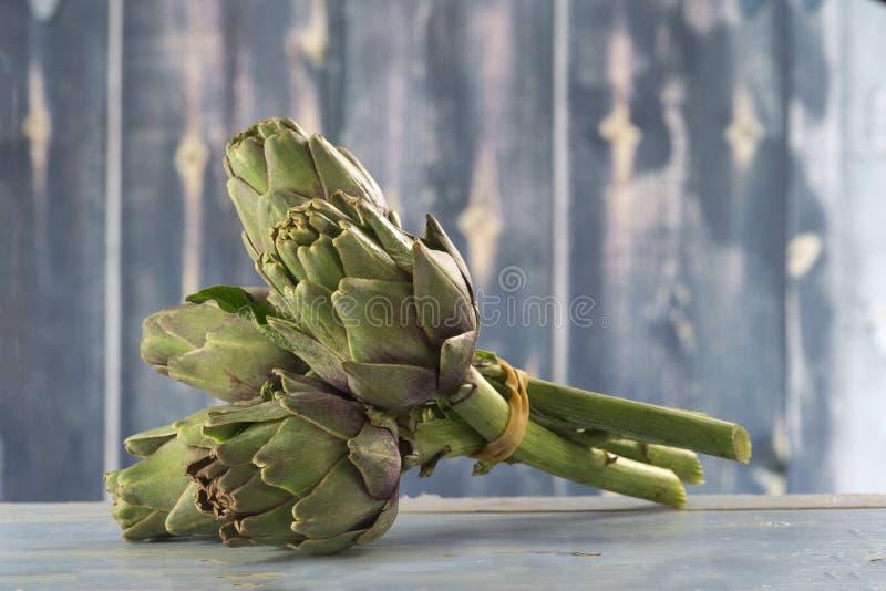 Alcachofas frescas con el tronco y la hoja imagenes de archivo