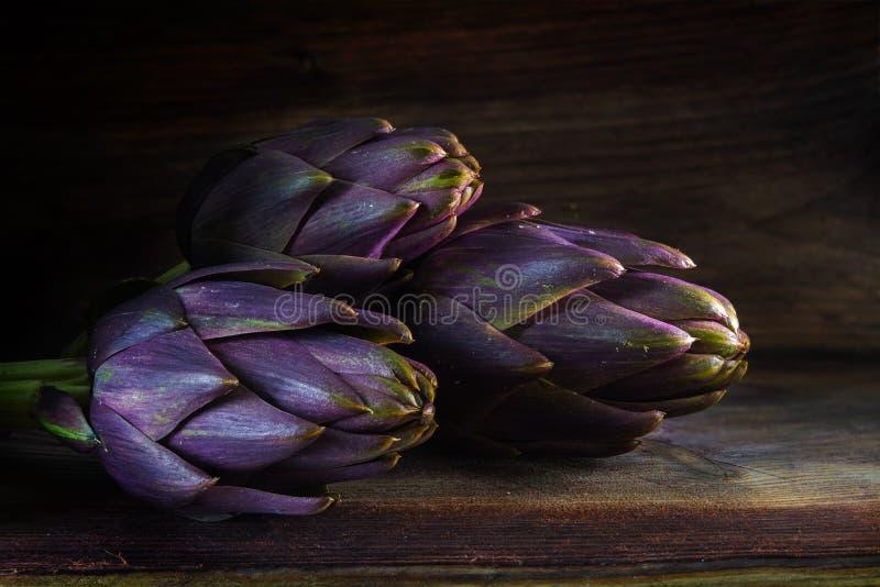 Alcachofas púrpuras de Italia en la madera rústica oscura fotografía de archivo
