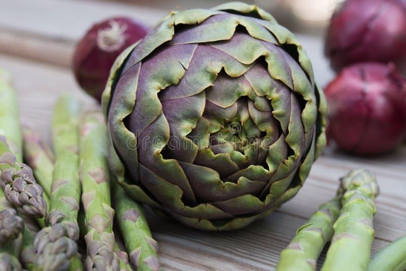 Alcachofra, aspargo, vegetais verdes da cebola vermelha e violetas saudáveis fotografia de stock