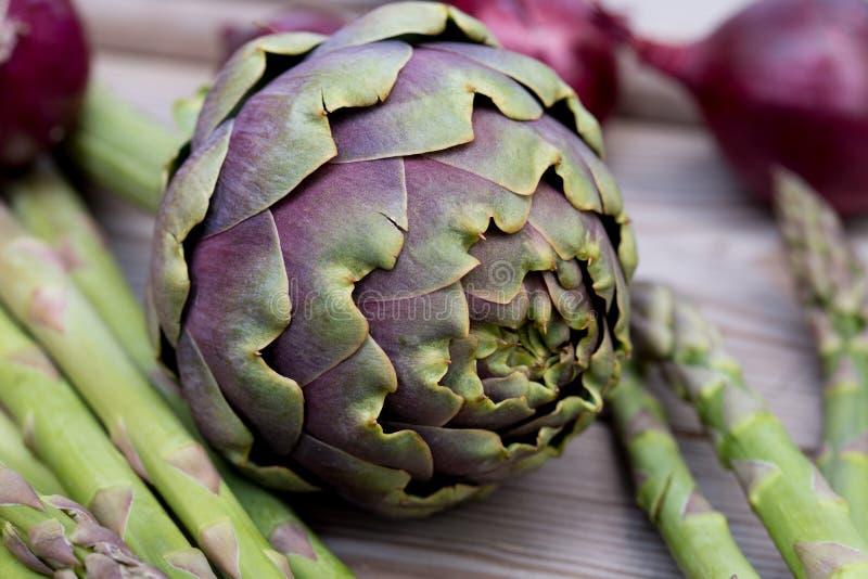 Alcachofra, aspargo, vegetais verdes da cebola vermelha e violetas saud?veis fotografia de stock