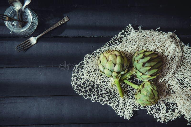Alcachofras verdes frescas da vista superior com material trançado da corda e de cozinha na tabela de madeira preta iluminada pel foto de stock royalty free