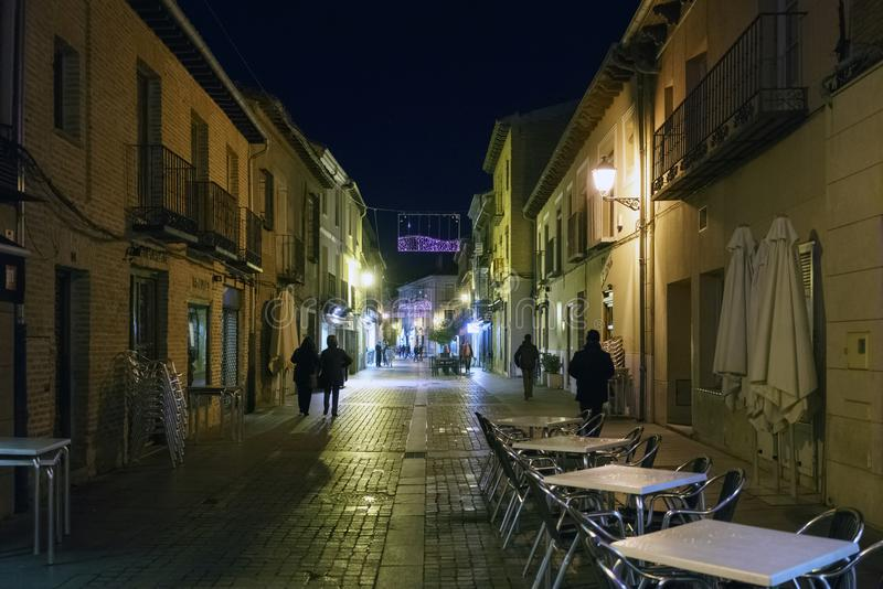 Alcala de Henares, Madrid, Spain / December 1, 2017: Night photo. Of a street in the old part of the town with purple Christmas lighting with bar tables in the royalty free stock images