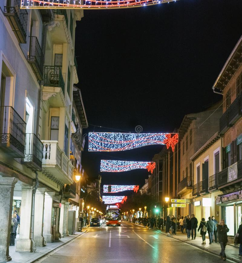 Alcala de Henares, Madrid, Spain / December 1, 2017: Night shot. Of a downtown street called `Libreros` with Christmas illumination of red and white LED lights stock photos