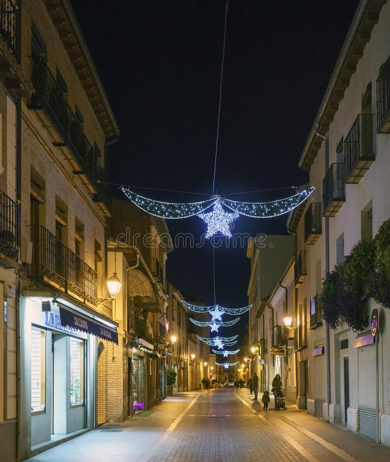 Alcala de Henares, Madrid, Spain / December 1, 2017: Night shot. Of a street in the center of town with white Christmas lights with a star and people walking royalty free stock photos
