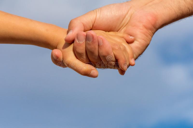 Alcance para fora em conjunto Um pai a suas mãos da posse da filha com um fundo do céu azul fotos de stock royalty free