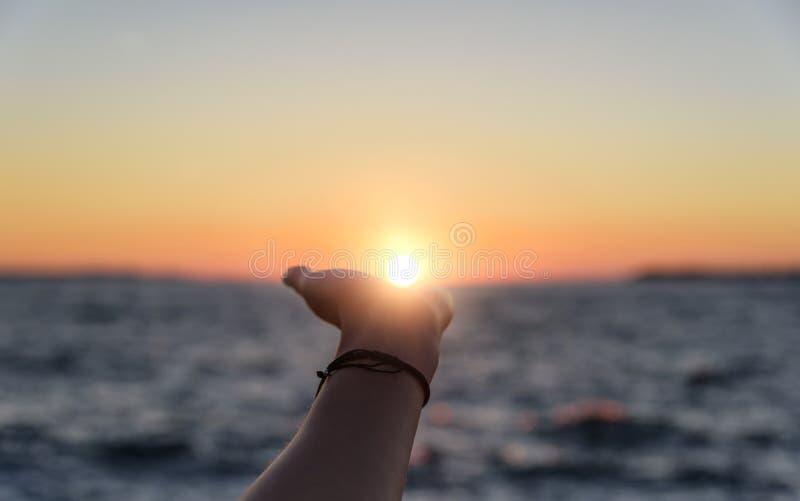 Alcances de la mano para el sol en la puesta del sol foto de archivo