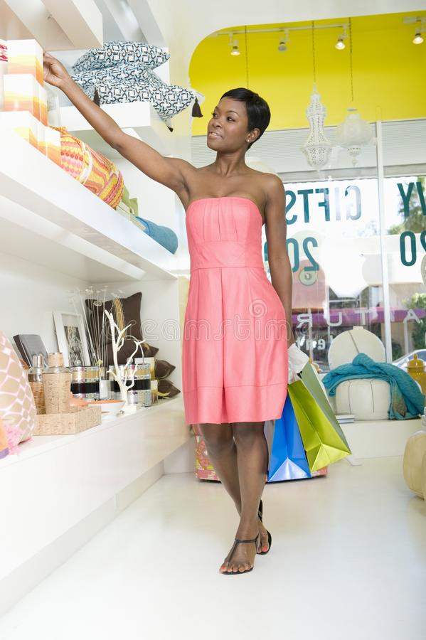 Alcances de la mujer para el producto en la tienda casera de los interiores foto de archivo libre de regalías