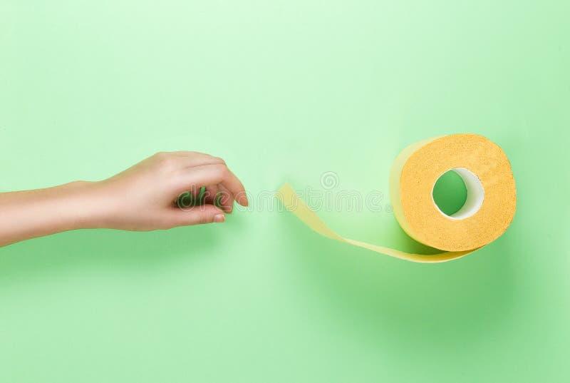Alcances fêmeas da mão para o rolo de toalete amarelo no fundo verde Configuração lisa Conceito do encanto da higiene Vista super imagem de stock