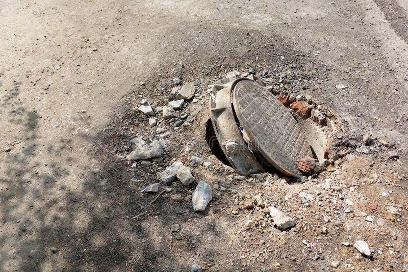 Alcantarilla quebrada en el camino Peligro de lesi?n Reparaci?n de comunicaciones foto de archivo