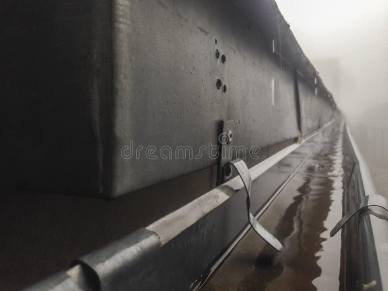 Alcantarillado del canal en el tejado con niebla del goteo fotografía de archivo libre de regalías