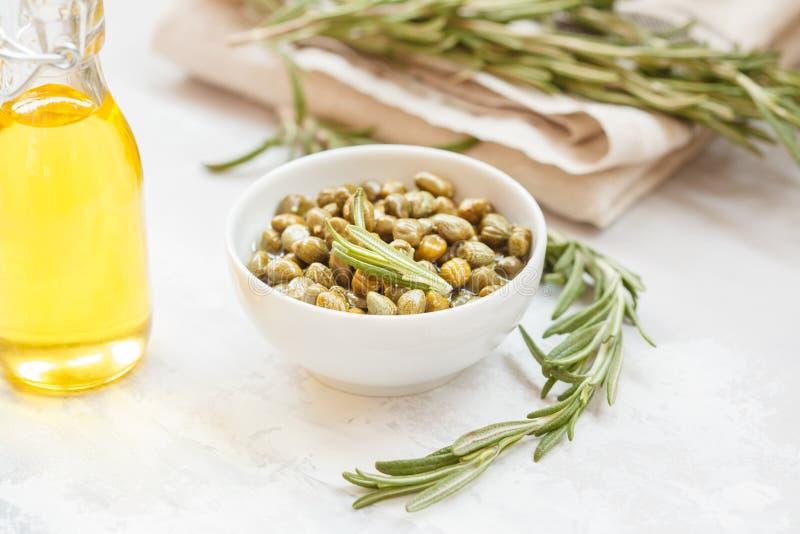 Alcaparras, azeite e alecrins em um fundo claro foto de stock