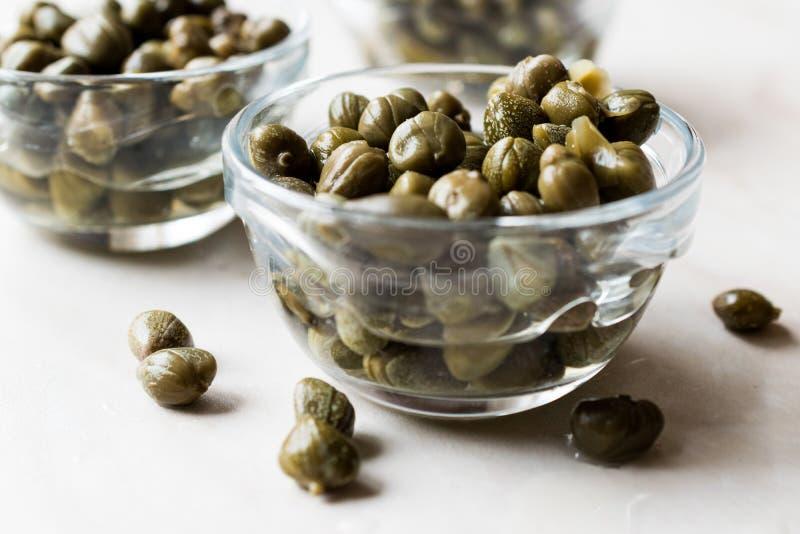 Alcaparras comestíveis na bacia de vidro pronto para comer fotos de stock