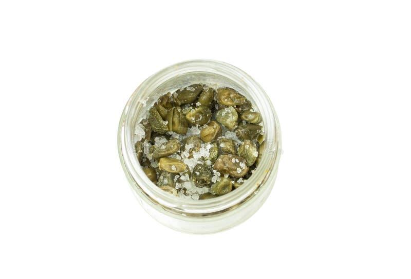Alcaparras verdes com sal grosso em um frasco de vidro isolado no fundo branco, vista superior Os vegetais salgados temperam o in fotos de stock