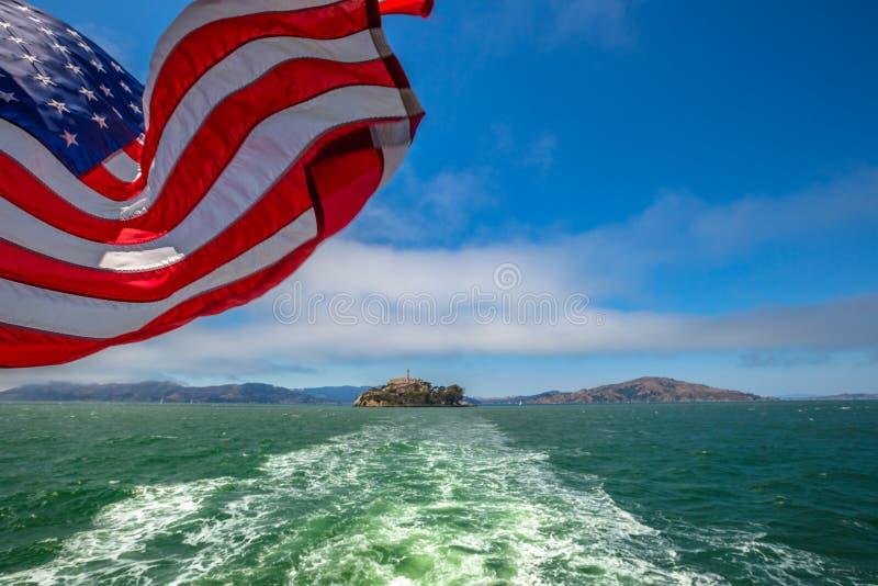 Alcatraz island and american flag. Alcatraz island boat trip in San Francisco Bay, California, United States. Ferry boat to Alcatraz with American flag waving stock photo