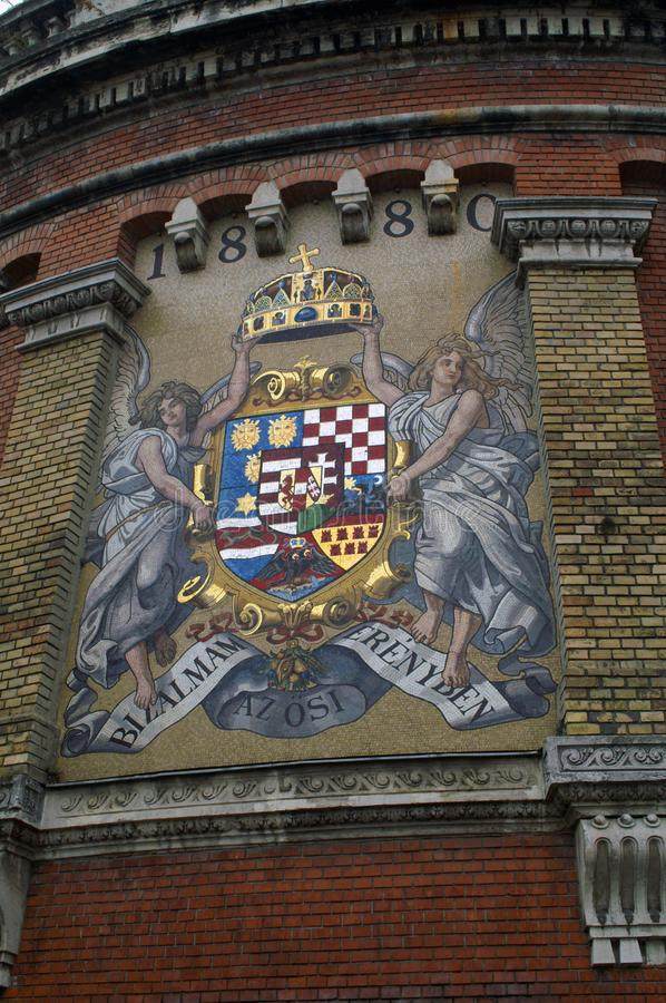 The coat of arms on the castle wall in the city of Budapest, Hungary. Coat of arms on a tower in the city of Budapest, Hungary. Two angels hold the crown over stock images