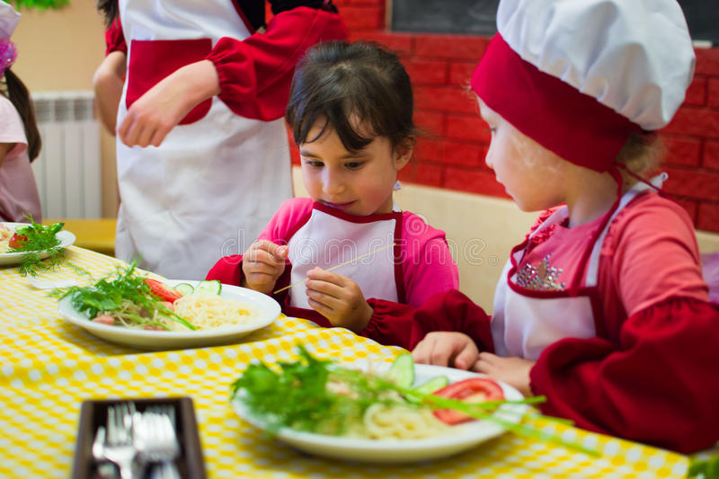 Alchevsk, Ουκρανία - 30 Ιουλίου 2017: Σχολικοί μάγειρες για τα παιδιά Μάθετε να μαγειρεύετε τα ζυμαρικά με τα λουκάνικα στοκ εικόνα