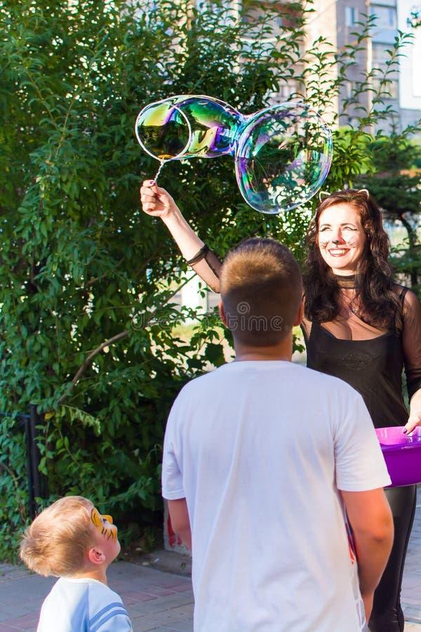 Alchevsk, Ucrânia - 3 de agosto de 2017: Partido do ` s das crianças, bolhas de sabão da captura fotografia de stock