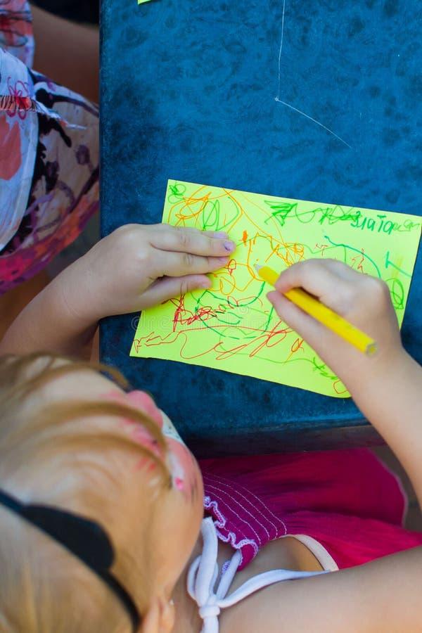 Alchevsk, Ucrânia - 3 de agosto de 2017: Um rapaz pequeno e uma menina estão tirando na tabela Vista de acima fotografia de stock