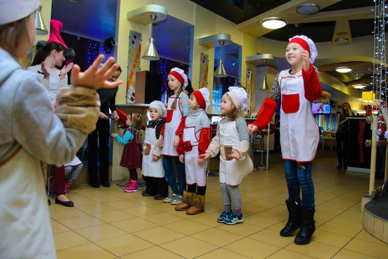 Alchevsk, Ucrânia - 14 de janeiro de 2018: crianças sob a forma do jogo dos cozinheiros com animadores fotografia de stock