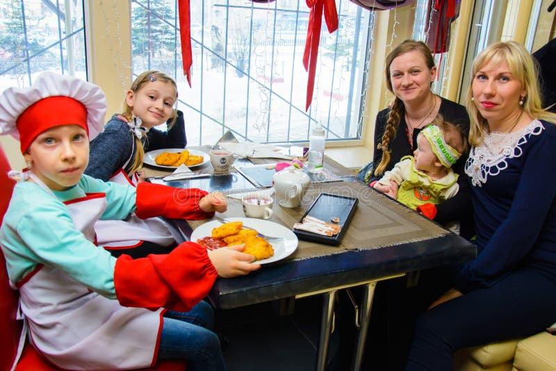 Alchevsk, Ucrânia - 11 de março de 2018: crianças sob a forma dos cozinheiros em cozinheiros pequenos da escola em um café foto de stock