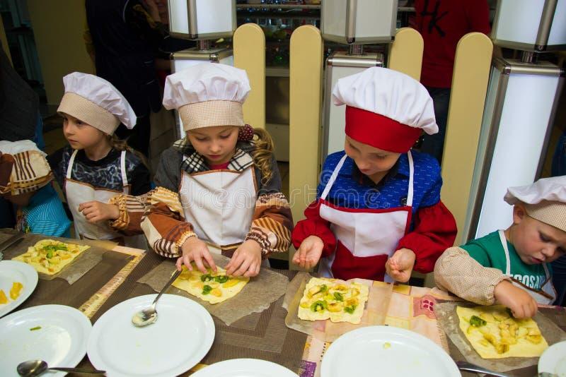 Alchevsk, Ucrânia - 15 de outubro de 2017: cozinheiros da escola para crianças em um café preparando a pizza do fruto imagens de stock
