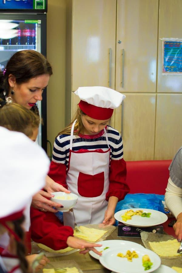 Alchevsk, Ucrânia - 15 de outubro de 2017: cozinheiros da escola para crianças em um café preparando a pizza do fruto fotografia de stock