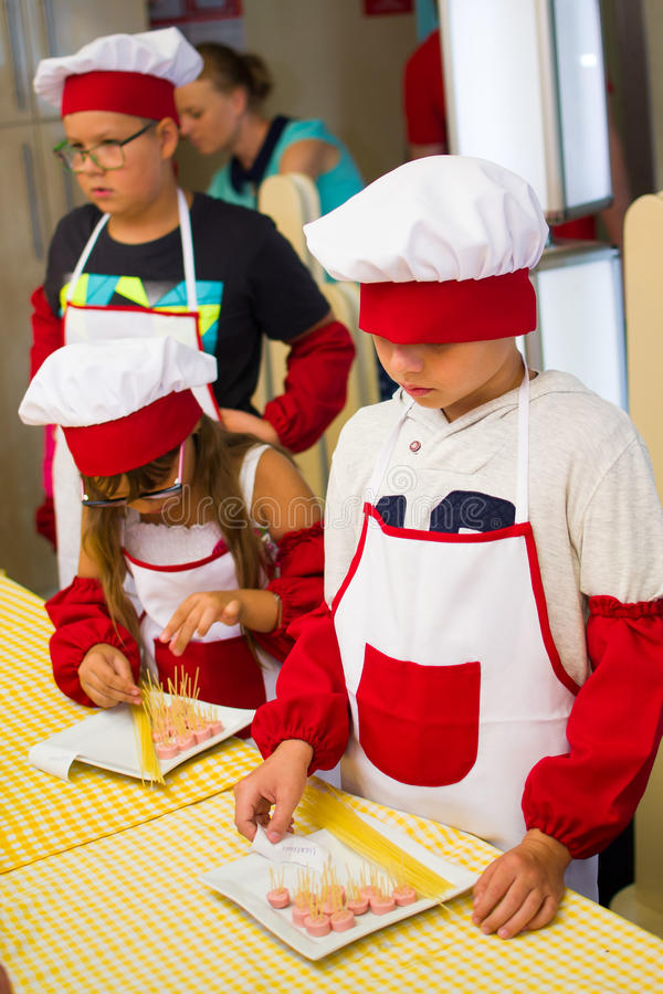 Alchevsk, Ucraina - 30 luglio 2017: Cuochi della scuola per i bambini Impari cucinare la pasta con le salsiccie immagine stock libera da diritti