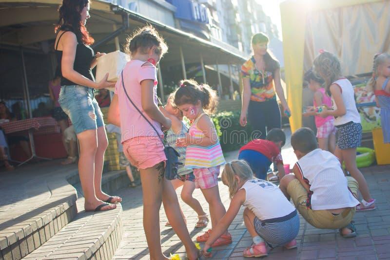 Alchevsk, Ucraina - 27 luglio 2017: Gioco di bambini felice con gli animatori di estate fotografie stock libere da diritti