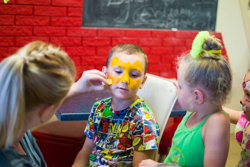 Alchevsk, Ukraine - 3 août 2017 : Un enfant dessine un visage pour une partie du ` s d'enfants Maquillage d'Aqua pour des filles  photographie stock