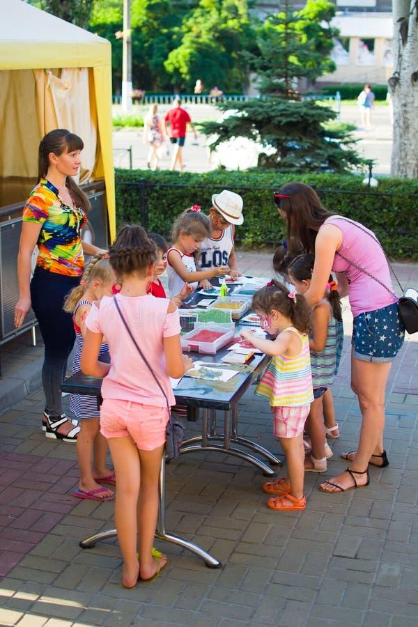 Alchevsk, Ukraine - 27 juillet 2017 : Les enfants peignent avec la colle et le sable coloré Partie du ` s d'enfants photos libres de droits
