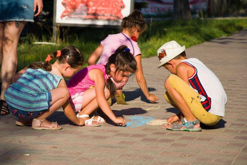 Alchevsk, Ukraine - 27 juillet 2017 : Les enfants peignent un pilier sur l'asphalte Partie du ` s d'enfants images stock