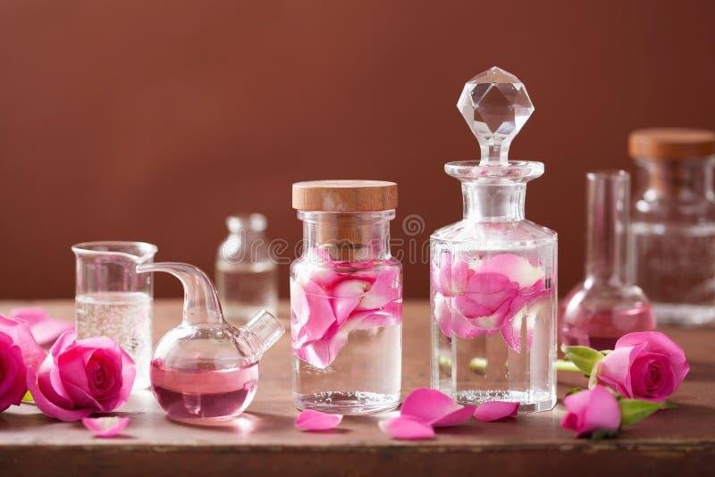 Alchimie, Aromatherapie mit rosafarbenen Blumen, Flaschen lizenzfreie stockbilder