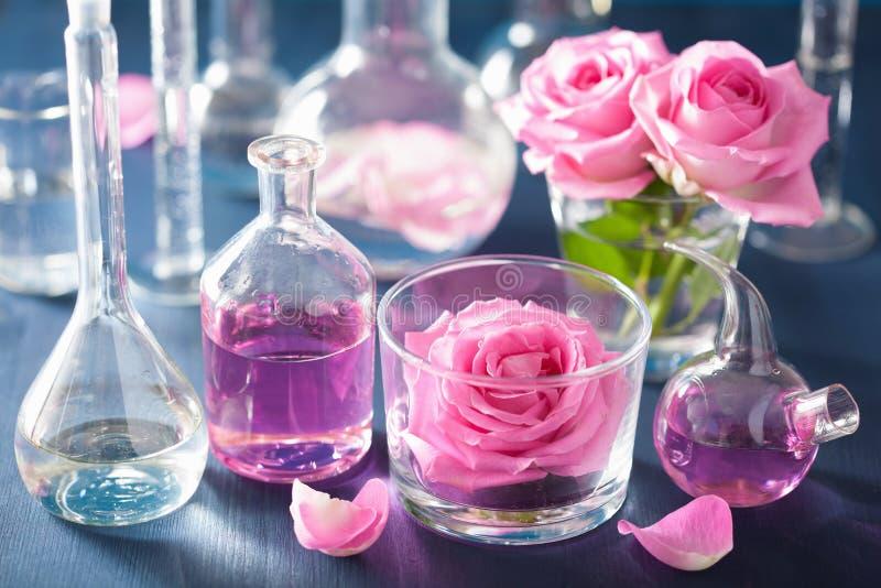 Alchimie und Aromatherapie mit rosafarbenen Blumen und chemischen Flaschen lizenzfreies stockbild