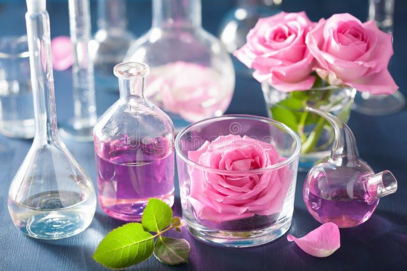 Alchimie- und Aromatherapiesatz mit rosafarbenen Blumen und chemischen flas lizenzfreies stockbild
