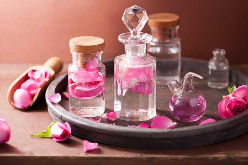 Alchimie- und Aromatherapiesatz mit rosafarbenen Blumen und Flaschen lizenzfreies stockbild