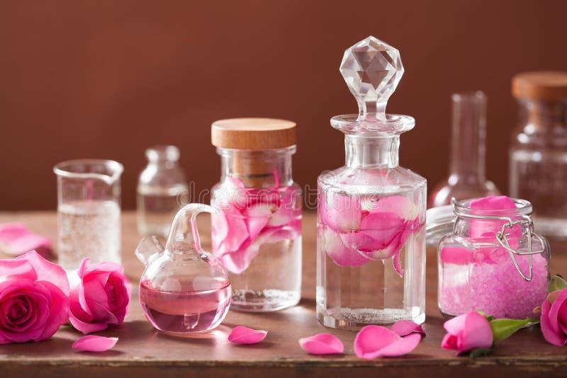 Alchimie- und Aromatherapiesatz mit rosafarbenen Blumen und Flaschen stockfotografie