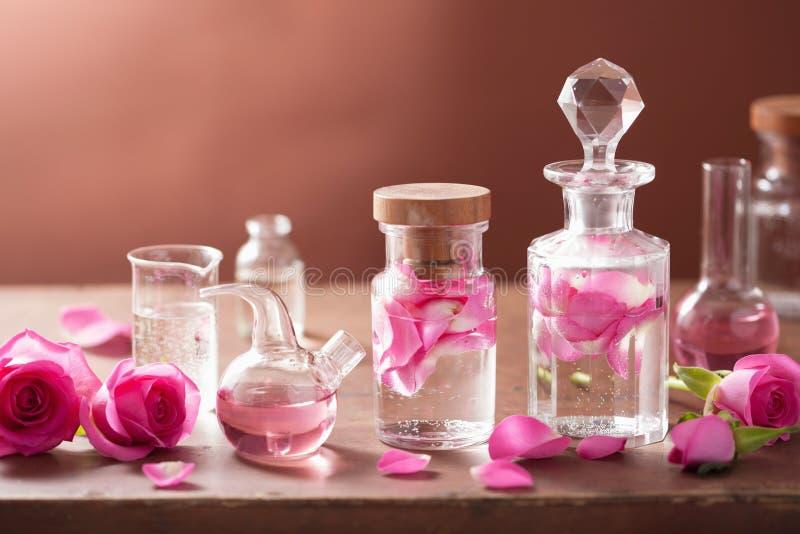 Alchimie- und Aromatherapiesatz mit rosafarbenen Blumen und Flaschen stockbild