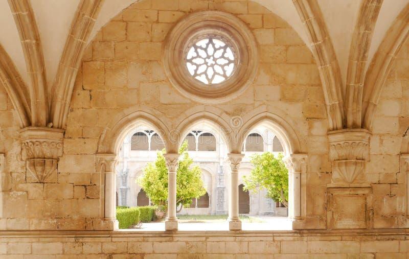 Alcobaca, Πορτογαλία - τον Αύγουστο του 2018: Η άποψη του κήπου μοναστηριών μέσω της αψίδας και αυξήθηκε παράθυρα του μοναστηριού στοκ εικόνες