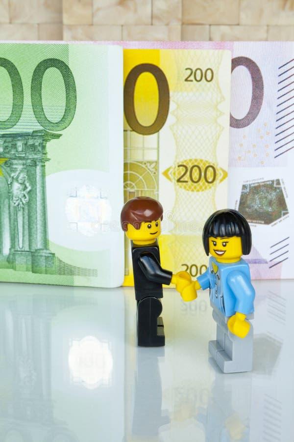 Alcobendas Spanien - Maj 14, 2018: Handskakningen för en överenskommelse på räkningbakgrund, Lego minifigures tillverkas av Legoe royaltyfri fotografi